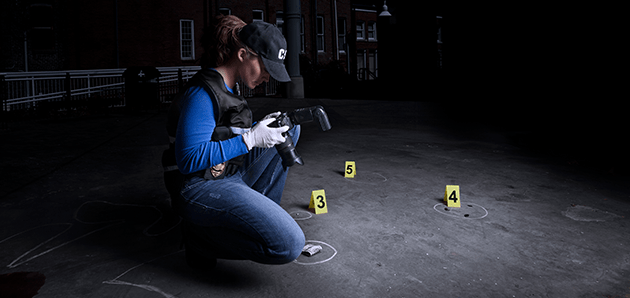 Forensic scientist taking photos at crime scene